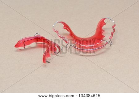 Red Tooth retainer for orthodontic on the brown background