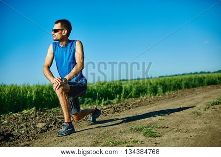 man runner athlete warming up before jogging along a green field in the early morning. man lunged forward on one knee. man fitness sunset jogging workout wellness concept. free space behind the man