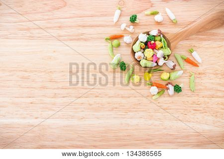 Variety of miniature clay vegetables on wooden spoon ; food and health concept background with copy space