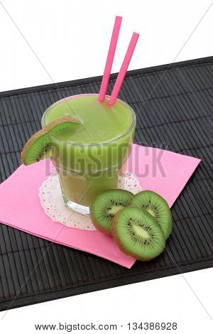 Kiwi smoothie health drink with fresh fruit on a bamboo mat over white background. High in vitamins and antioxidants.
