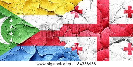 Comoros flag with Georgia flag on a grunge cracked wall