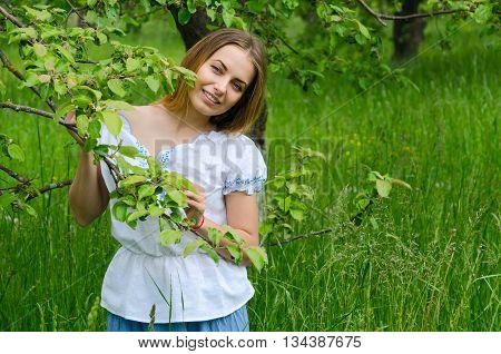 Portrait of young beautiful woman in apple orchard