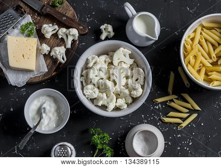 Raw ingredients for cooking pasta with roasted cauliflower - pasta cauliflower cheese cream on dark stone background.