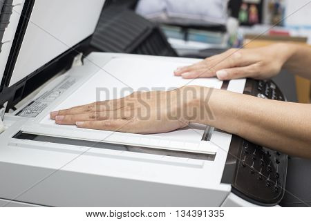 woman hands putting a sheet of paper into a copying device