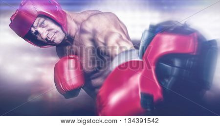 Rear view of boxer standing against composite image of boxing ring
