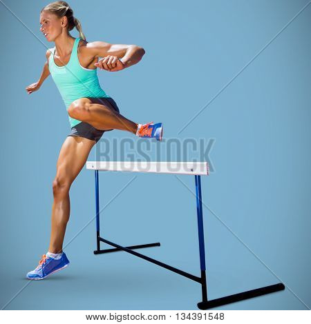 Sportswoman practising the hurdles against blue background
