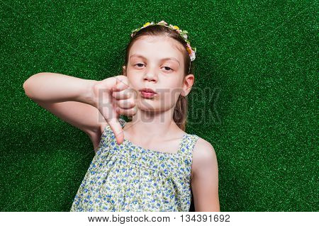 Little girl is lying on artificial grass and showing thumb down.
