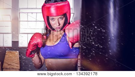 Portrait of pretty boxer with fighting stance against gym