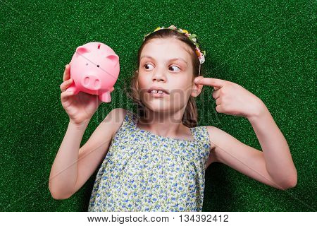 Little girl is lying on artificial grass and pointing at her piggy bank