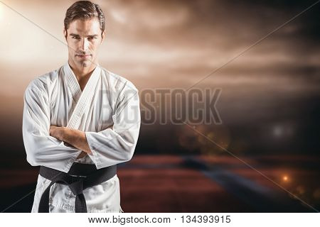 Portrait of fighter standing on black background against view of sport ground outdoor