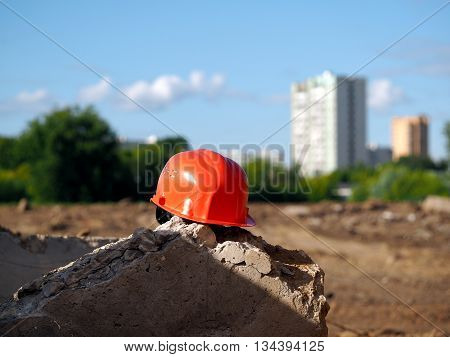Orange helmet on a background of a vacant lot. A lot of sun. In the distance city high-rise buildings trees. Wasteland - a place under construction