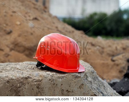Orange helmet on a concrete block. Background - a mountain of sand green trees