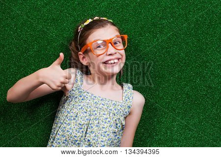Happy little girl is lying on artificial grass and showing thumb up.