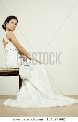 Bride with white wedding change purse on light background