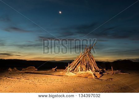 Drift wood shelter at night time with the moon too.