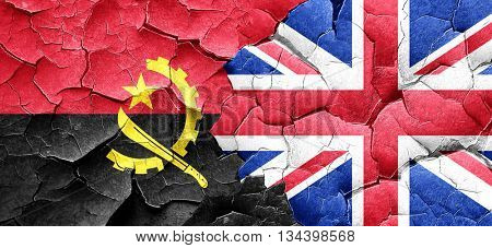 Angola flag with Great Britain flag on a grunge cracked wall