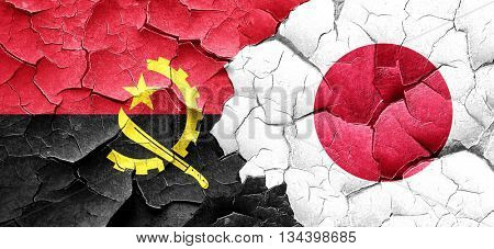 Angola flag with Japan flag on a grunge cracked wall