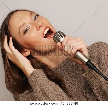 Happy singing girl. Beauty woman  with microphone over white background.