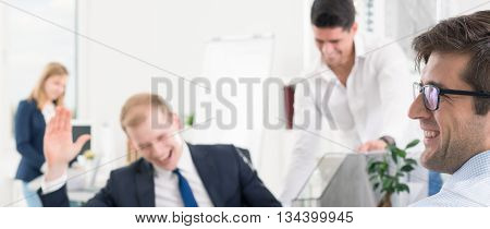 Blurry panoramic image of laughing workmates in a very bright office space
