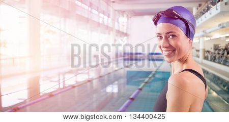 Fit swimmer standing by the pool smiling at camera at the leisure center