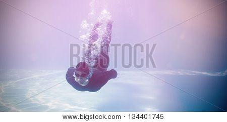Man wearing wetsuit while swimming underwater