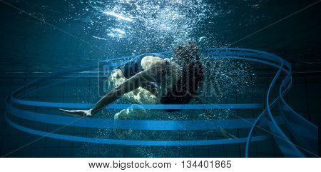 Athletic swimmer doing a somersault underwater against feet of woman standing on the edge of the pool