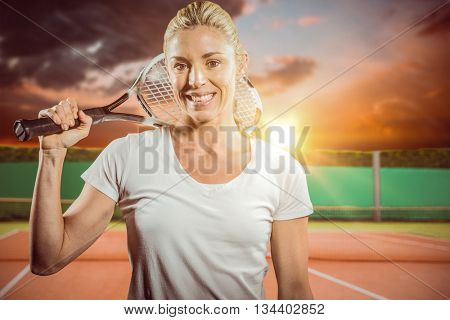 Portrait of female tennis player posing with racket against digitally generated image of tennis court