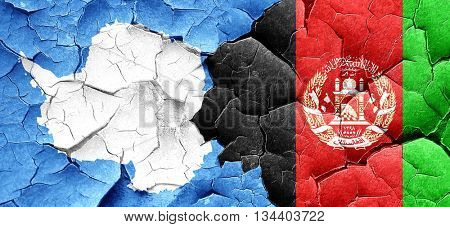 antarctica flag with afghanistan flag on a grunge cracked wall