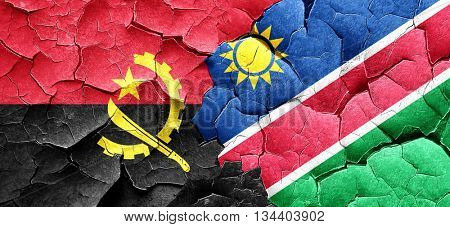 Angola flag with Namibia flag on a grunge cracked wall