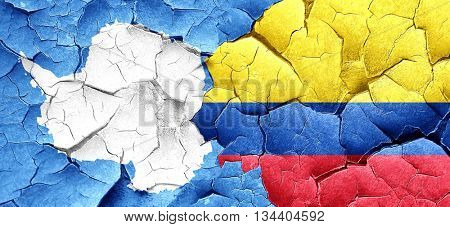 antarctica flag with Colombia flag on a grunge cracked wall