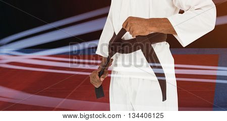 Fighter tightening karate belt against overhead view of playing field