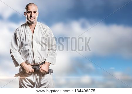 Fighter tightening karate belt against blue sky with clouds