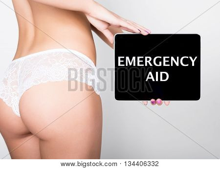 technology, internet and networking - close-up ass of girl in lacy lingerie, holding a tablet pc with emergency aid sign. Adult content.
