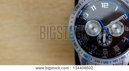 One wristwatch on wooden background. calendar and seconds, minutes and hours hands