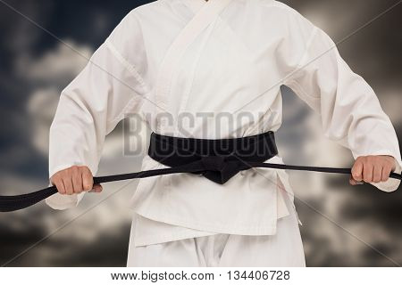 Fighter tightening karate belt against dark sky with white clouds