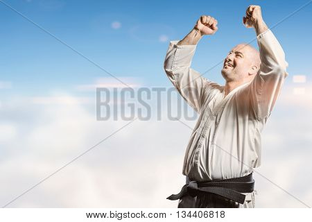 Fighter posing after victory against blue sky over clouds