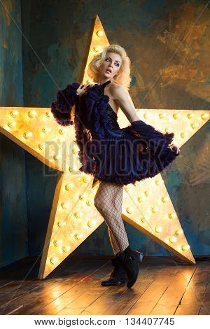 Beautiful playful adult blonde woman wearing dark blue lace skirt and mesh stockings posing over dark background with glowing star. Actress playing on stage. Theatre or dancer.