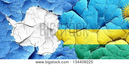 antarctica flag with rwanda flag on a grunge cracked wall