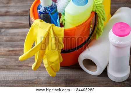 Plastic bucket with cleaning supplies on wood background
