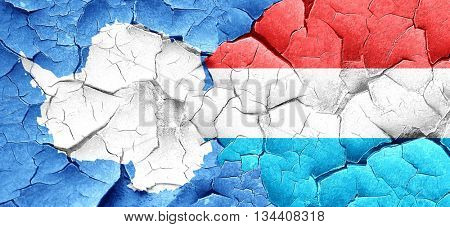 antarctica flag with Luxembourg flag on a grunge cracked wall