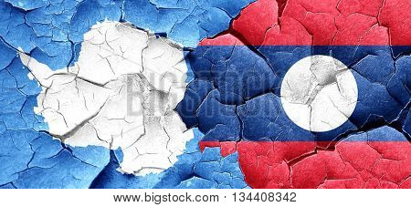 antarctica flag with Laos flag on a grunge cracked wall
