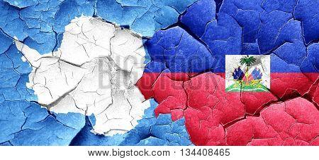 antarctica flag with Haiti flag on a grunge cracked wall