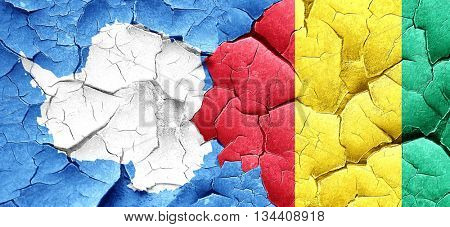 antarctica flag with Guinea flag on a grunge cracked wall