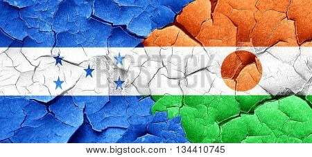 Honduras flag with Niger flag on a grunge cracked wall