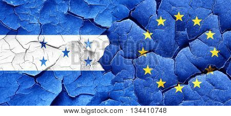 Honduras flag with european union flag on a grunge cracked wall