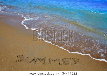 Summer spell written word in sand of a beach in vacation