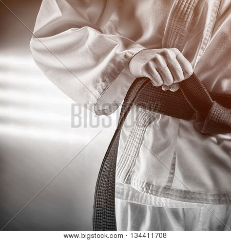 Fighter tightening karate belt against spotlights