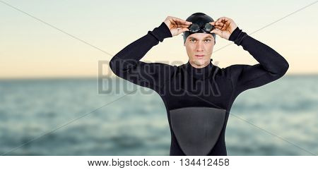 Swimmer in wetsuit wearing swimming goggles against beautiful day in the water