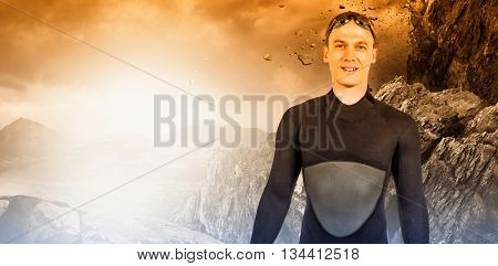 Portrait of swimmer in wetsuit against rock crashing down from cliff