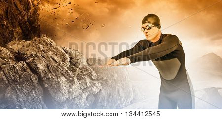 Swimmer in wetsuit while diving against rock crashing down from cliff
